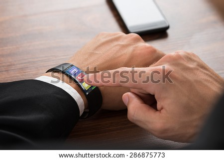 Close-up Of Businessman's Hand Wearing Smartwatch Pressing Call Button - stock photo