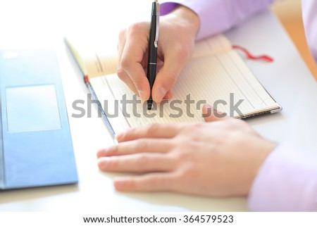 Close up of businessman's hands writing a note in a notepad - stock photo