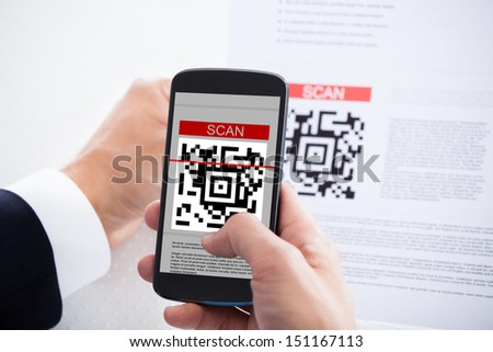 Close-up Of Businessman Scanning A Barcode Using Cell Phone - stock photo