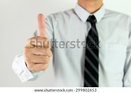 Close up of businessman showing thumb up - stock photo