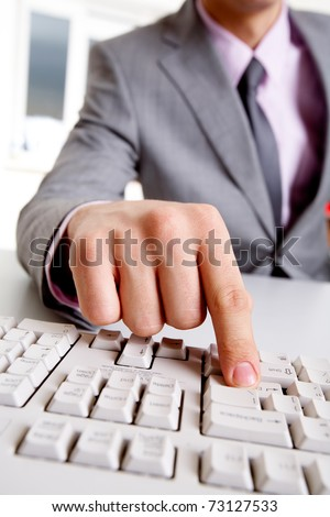 Close-up of businessman sitting at the table and typing a letter - stock photo
