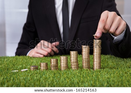 Close-up Of Businessman Stacking Coins Over Grass - stock photo