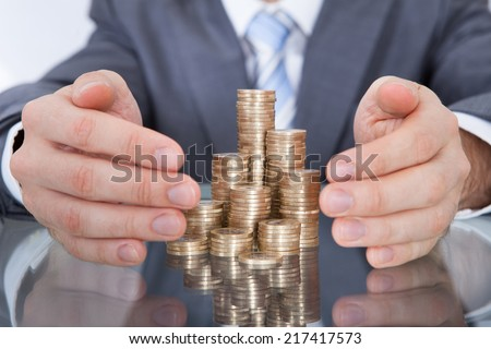 Close-up Of Businessman Taking Care Of Golden Stack Coin - stock photo
