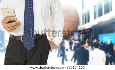 close up of businessman using smart phone with crowd of business people background - stock photo