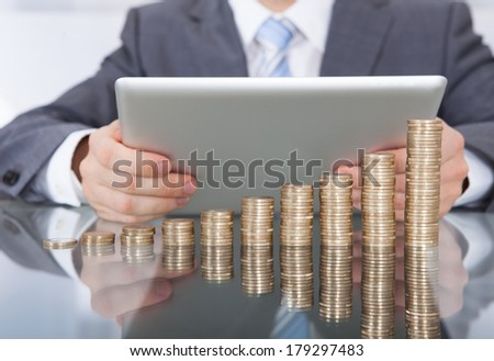 Close-up Of Businessman With Digital Tablet In Front Of Golden Coin Stack - stock photo