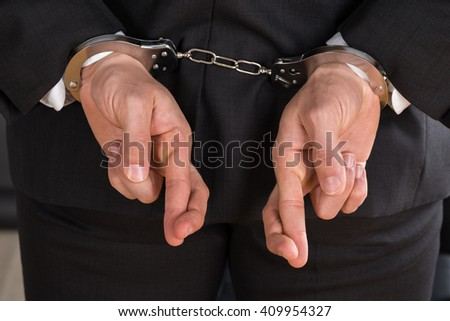 Close-up Of Businessman With Handcuffs And Finger Crossed. Crossed Fingers As A Symbol Of Breach Of Contract - stock photo