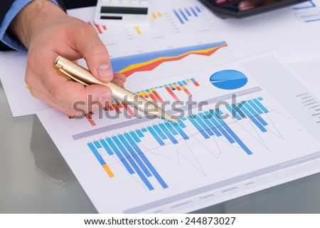 Close-up Of Businessman With Pen And Calculator Analyzing Graph - stock photo