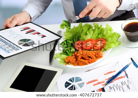 Close-up of businessman working on marketing strategy during business lunch. - stock photo