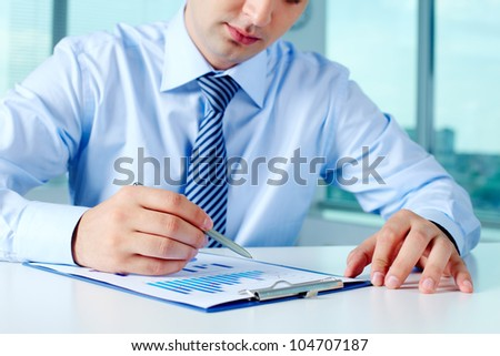 Close-up of businessman working with financial document - stock photo