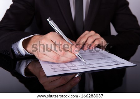 Close-up Of Businessman Writing On Paper With Pen - stock photo