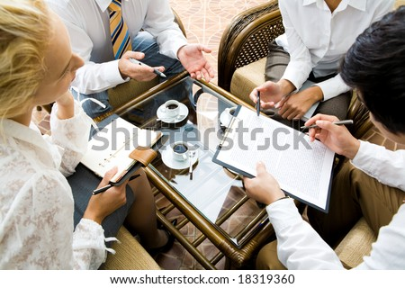 Close-up of businesspeople discussing a plan at meeting - stock photo