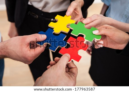 Close-up Of Businesspeople Holding Multi Colored Jigsaw Puzzle - stock photo