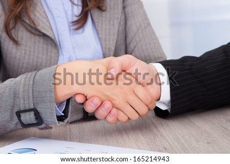 Close-up Of Businesspeople Shaking Hands At Office Desk - stock photo