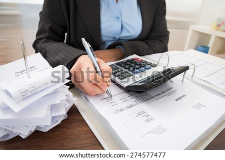 Close-up Of Businessperson Calculating Bills At Desk - stock photo