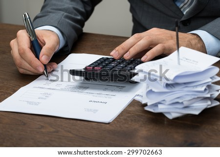 Close-up Of Businessperson Calculating Financial Expenses In Office - stock photo