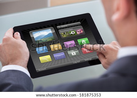 Close-up Of Businessperson Hand Over Icons On Digital Tablet - stock photo