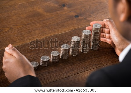 Close-up Of Businessperson Hand Protecting Stacked Coins On Wooden Desk - stock photo