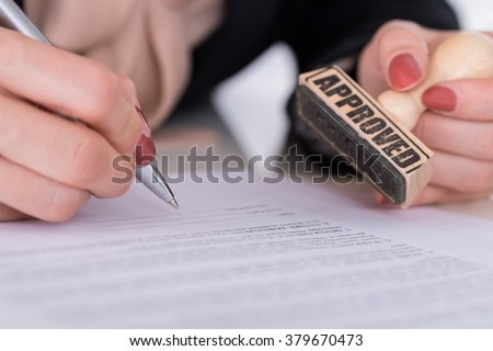 Close-up Of Businessperson Hand With Pen And Wooden Stamp On Document - stock photo