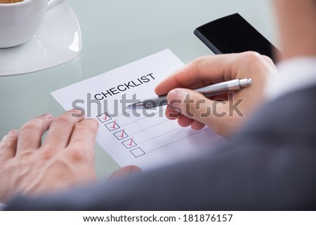 Close-up Of Businessperson Hand With Pen Marking A Check Box - stock photo