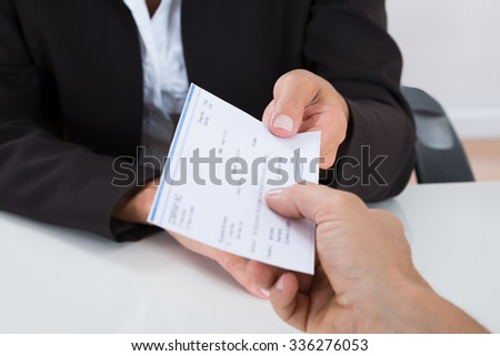 Close-up Of Businessperson Hands Giving Cheque To Other Person At Desk - stock photo