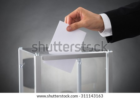 Close-up Of Businessperson Hands Putting Ballot In Box At Desk - stock photo
