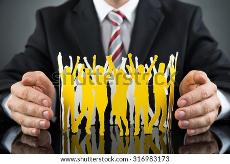 Close-up Of Businessperson Protecting Cheering Paper Cutout People At Desk - stock photo