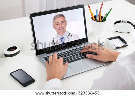 Close-up Of Businessperson Videochatting With Doctor On Laptop At Desk - stock photo