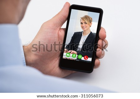 Close-up Of Businessperson Videochatting With Female Colleague On Mobile Phone - stock photo