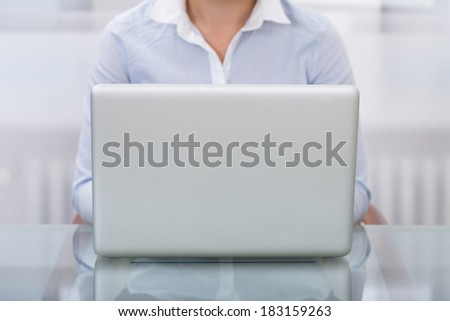 Close-up Of Businessperson Working On Laptop At Workplace - stock photo
