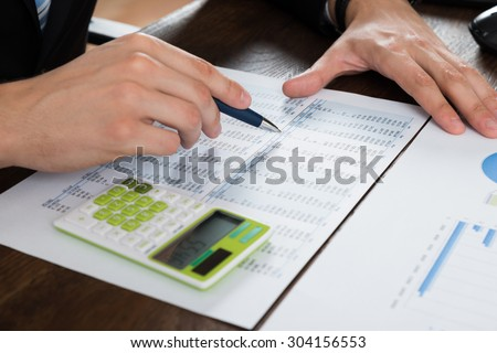 Close-up Of Businessperson Working With Accounting Document At Desk - stock photo