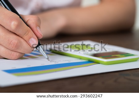 Close-up Of Businesswoman Analyzing Graph With Calculator At Desk - stock photo
