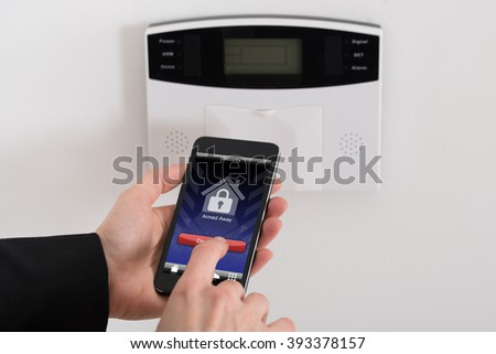 Close-up Of Businesswoman Hand Disarming Security System Of Door - stock photo