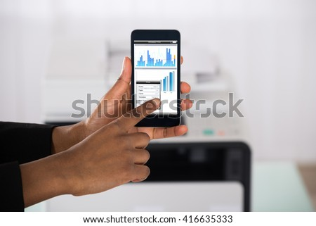 Close-up Of Businesswoman Hand Using Smartphone For Printing Graph Paper - stock photo