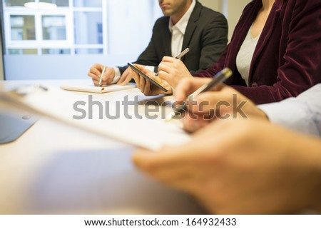 Close-up of Businesswoman hands working with stylus on tablet pc during a meeting - stock photo