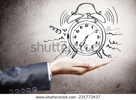 Close up of businesswoman holding alarm clock in palm - stock photo