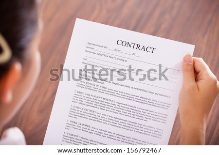 Close-up Of Businesswoman Holding Contract Paper In Hand - stock photo