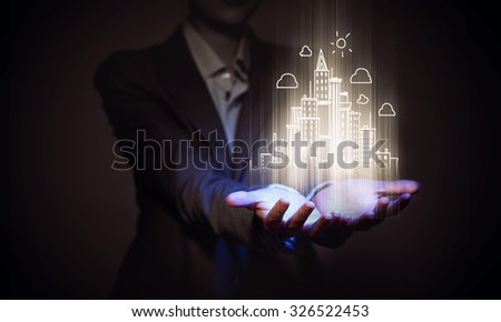Close up of businesswoman holding digital construction project in palms - stock photo
