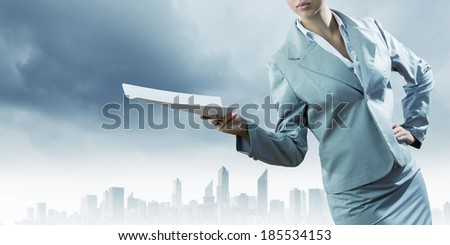 Close up of businesswoman holding papers in hands - stock photo