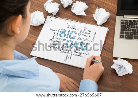 Close-up Of Businesswoman Planning For Bigdata At Desk In Office - stock photo