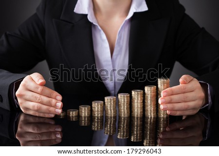 Close-up Of Businesswoman Protecting Golden Coins With Hand - stock photo