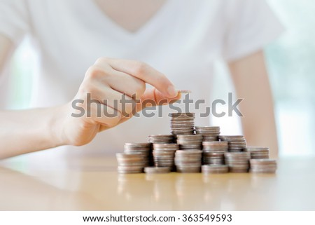 Close-up Of Businesswoman Putting Coin To Rising Stack Of Coins - stock photo