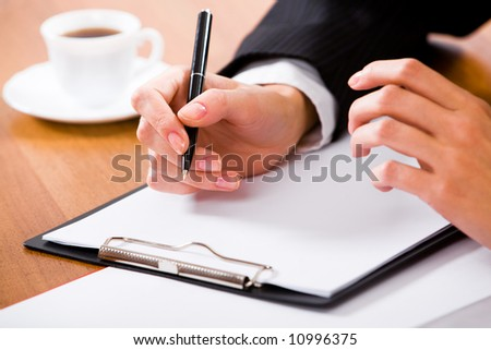 Close-up of businesswoman's hand holding pen over white paper with a cup of coffee near by - stock photo