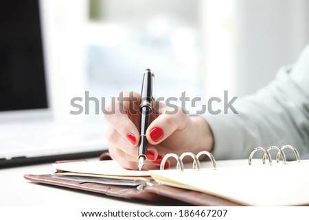 Close-up of businesswoman's hand while writing note in diary. Small business. - stock photo
