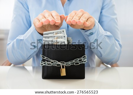 Close-up Of Businesswoman Saving Banknote In Wallet With Lock - stock photo