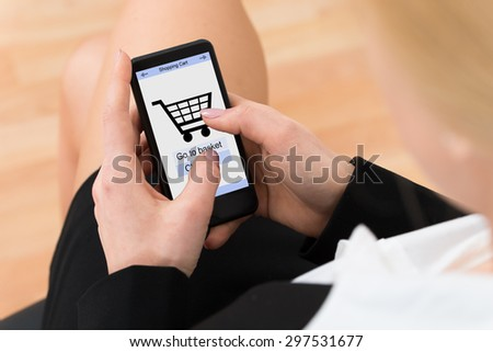 Close-up Of Businesswoman Shopping Online On Mobile Phone In Office - stock photo