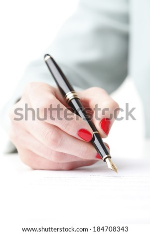 Close-up of businesswoman sitting at desk and fill form with fountain pen. Small business. - stock photo