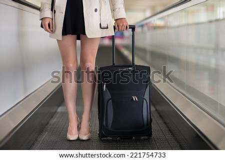 Close up of businesswoman with trolley standing on treadmill. - stock photo