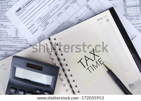 Close up of calculator, pen, tax form and agenda - stock photo