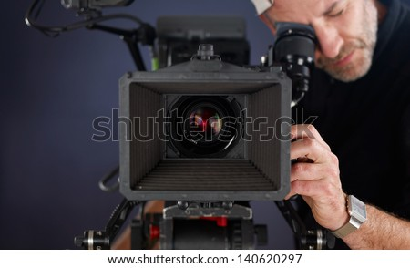 close-up of camera operator working with a cinema camera - stock photo