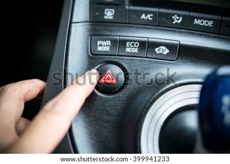 Close up of car emergency button with forefinger - warning button in a car.  - stock photo